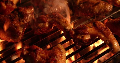 Temptingly spicy chicken wings being grilled over the bright glowing coals of a night time barbecue in Slow Motion