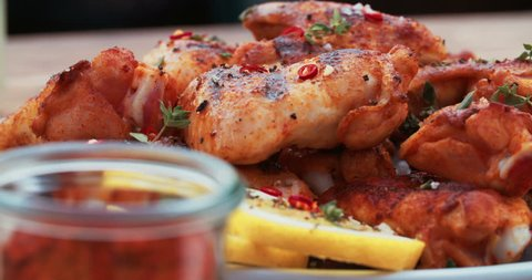 Plate of spicy chicken wings with lemon slices and a bowl of paprika powder alongside on a wooden table
