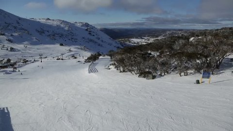 Australian snow fields at Blue Cow resort. View in front of resort looking towards distant tree covered mountains