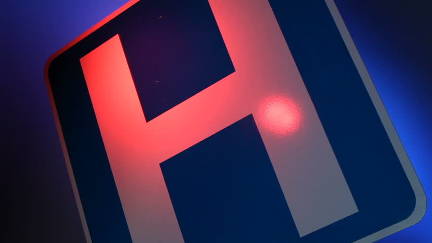 A close up of a hospital sign with flashing red and blue lights reflected on the sign