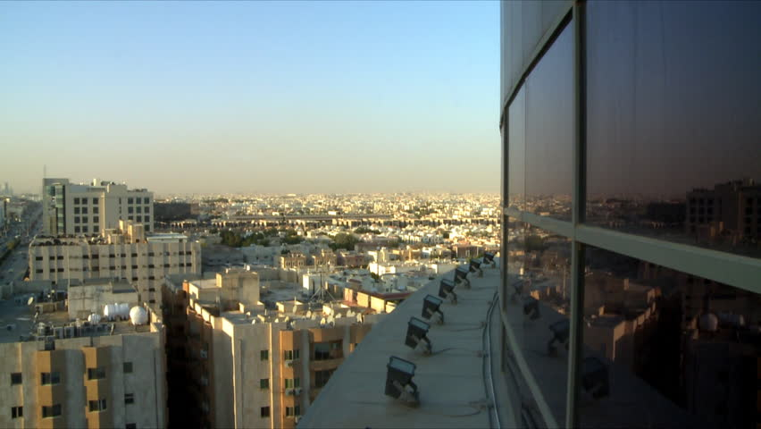 A pan showing the capital city of Riyadh, Kingdom of Saudi Arabia with clear blue skies and showing a busy main road and the Kingdom Centre in the distance