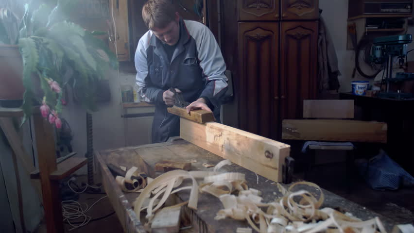 Hard working man is working in his shop on the plank of wood on the bench, footage is taken in slow motion.