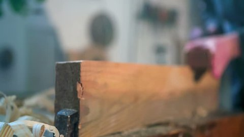 Close up footage of a man working on the wooden plank on the working bench, close up footage taken in slow motion.
