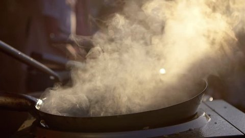 SLOW MOTION: cook makes asian noodles in wok. A versatile round-bottomed cooking vessel, originating from China. Asian food cooking.
