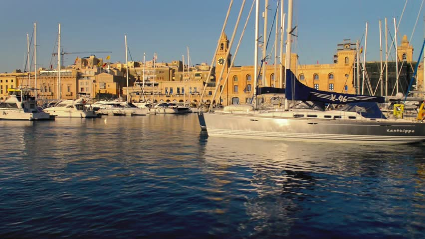 Vittoriosa, Valletta Grand Harbor, Malta  - 2 August 2015: marina in Vittoriosa with moored yachts and passenger boats, with Maritime Museum as a backdrop. Video filmed from water taxi