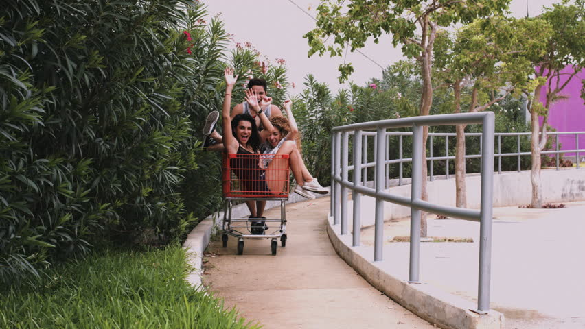 Male and female friends playing with shopping trolley on pavement