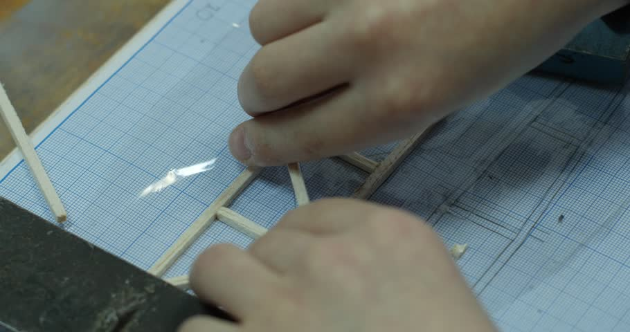 Child's hands are making the toy, model using the drawing on a graph paper, Children's avia modelling laboratory, construction of avia model of plane, construction of aircraft, children are building