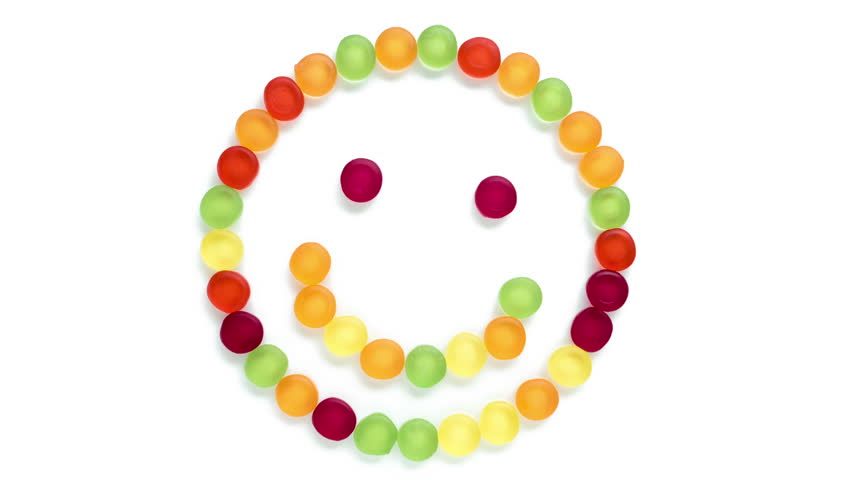 Smiley face made from sweets. Smiley face isolated on white made from different colored gum sweets.