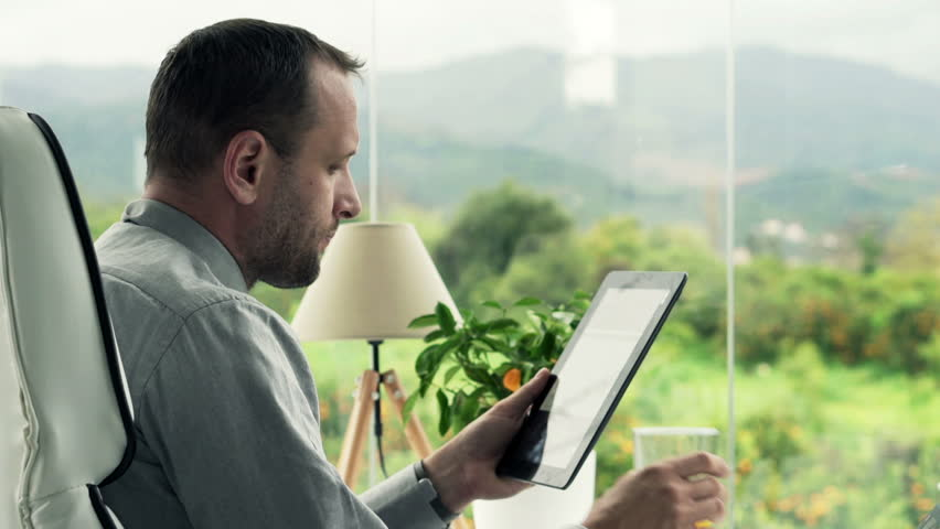 Businessman reading something on tablet computer and drinking beverage in office  | Shutterstock HD Video #11306069