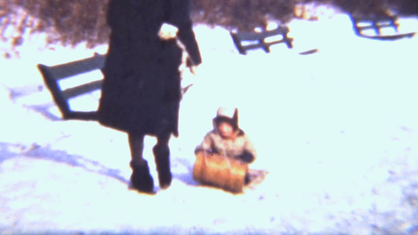 A cute little girl goes tobogganing with her mom on a sunny winter's day. from 8mm reels