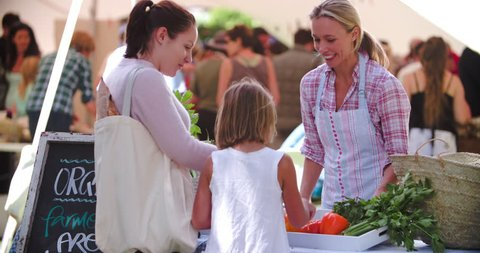 Mother and daughter buying vegetables at a market stall