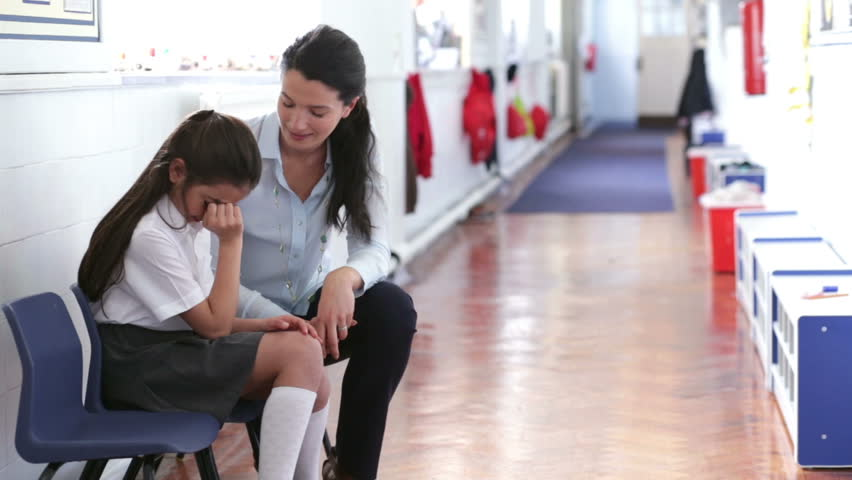 A teacher offers support as a young female student looks distressed and upset in the corridor. She has her hands up to her face and the female teacher has her arm around her.