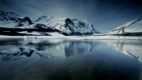 Lake with Ice reflecting snow covered mountains, Banff NP, Canada