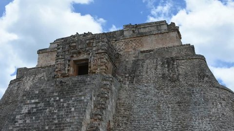 Medium time lapse shot of top of Mayan Pyramid of the Magician in Uxmal with clouds rapidly drifting in sky