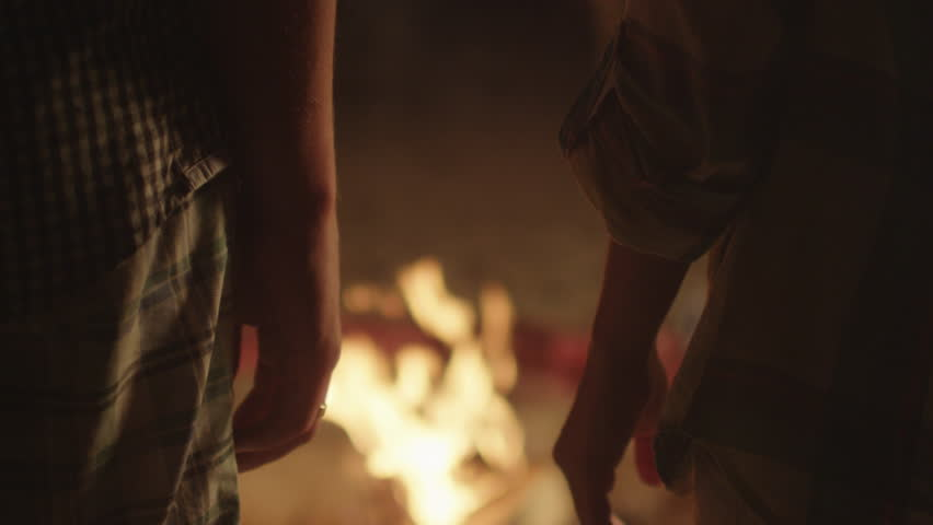 Couple is Holding Hands near Campfire at Night. Shot on RED Cinema Camera in 4K (UHD).