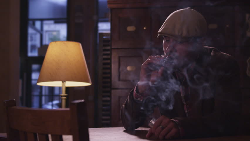 Man Smokes a Cigar blowing smoke puffing wealthy successful male