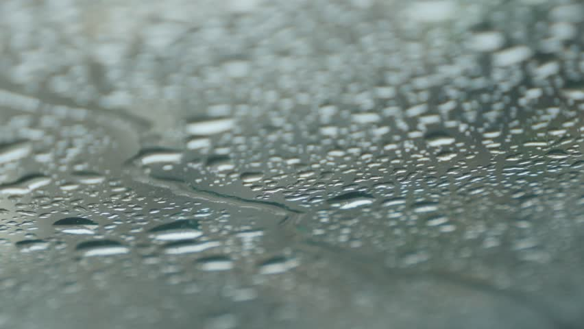 Raindrops falling on car windshield glass shallow DOF 4K 2160p 30fps UltraHD footage - Windscreen under strong rain falling 4K 3840X2160 UHD video