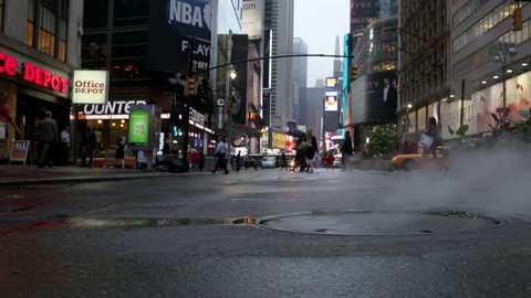 NEW YORK - MAY 24, 2012: steaming sewer cover and puddle on Broadway on rainy day with people with umbrellas in Midtown Manhattan, NY. Midtown Manhattan is a busy commercial area of New York City.