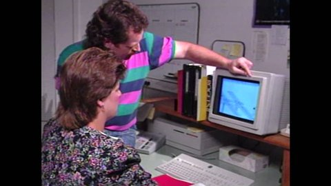UNITED STATES 1990s: Man and woman look at computer.