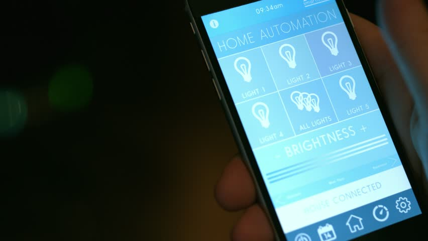 Smart Home technology - smart house, home automation, device with app icons. Man uses his smart phone with smart home app to turn on the lights in his house. IOT technology (Shot on RED)