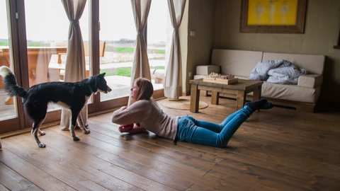 Woman lay on floor and play with dog 4K. Wide shot of living room in old traditional home with big futuristic bright windows and couch in background. Cute puppy and attractive female person.
