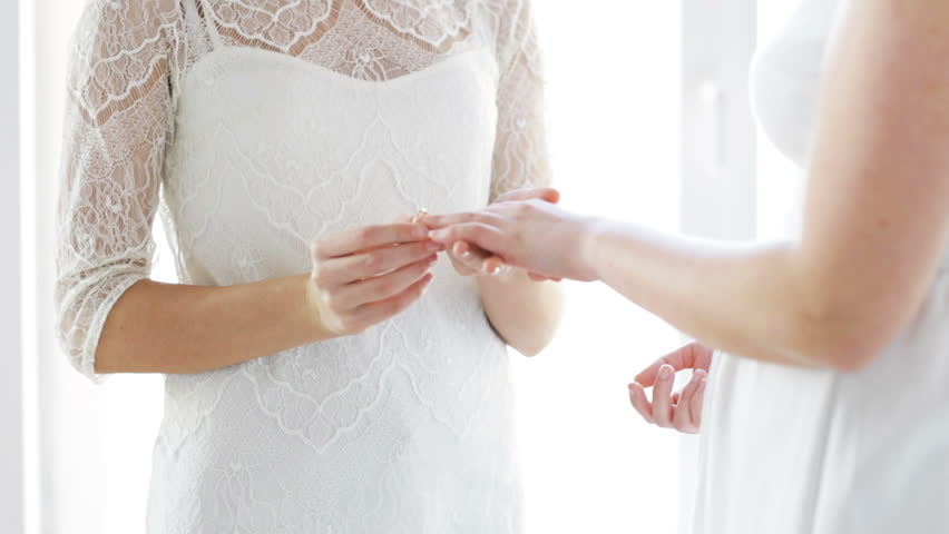 People, homosexuality, gay, same-sex marriage and love concept - close up of happy lesbian couple hands putting wedding ring on | Shutterstock HD Video #11470766