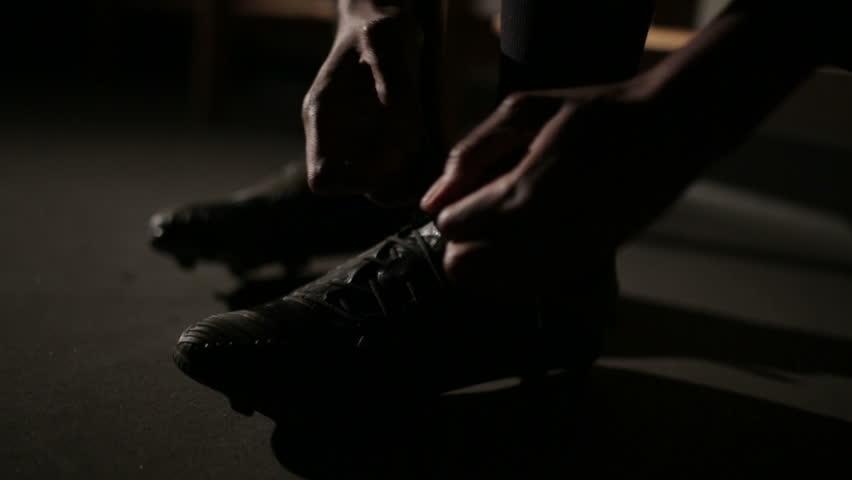 Footballer tying football boots preparing for a football soccer match