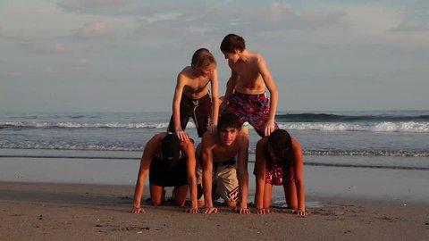 Family making a human pyramid at the beach