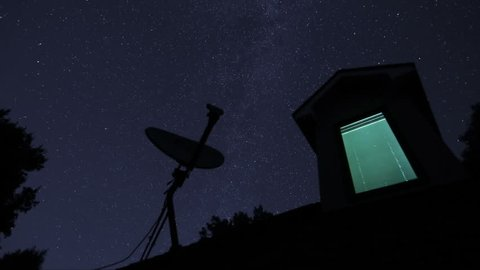 Time-lapse stars over house dormer window and satellite dish