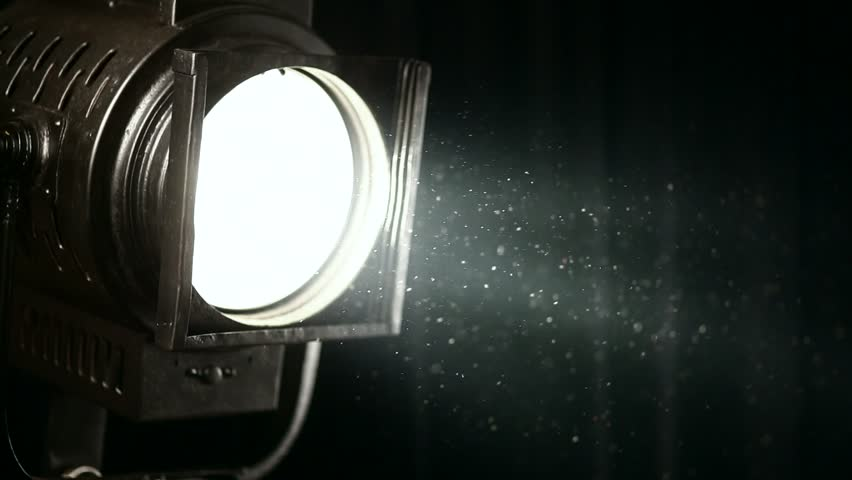 vintage theater spot light on black curtain with dust floating in front