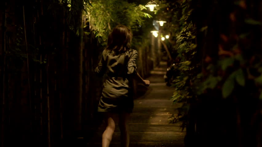 Afraid, scared woman running through narrow path at night, slow motion shot at 100fps