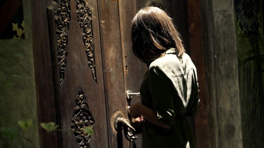 Girl Walks Into Door : Woman knocking on wooden door and walking into the