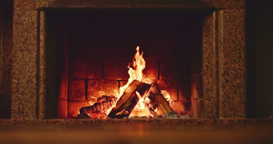 Slow motion fireplace burning. Warm cozy fireplace with real wood burning in it. Slow motion 120fps. 4k graded from RAW.