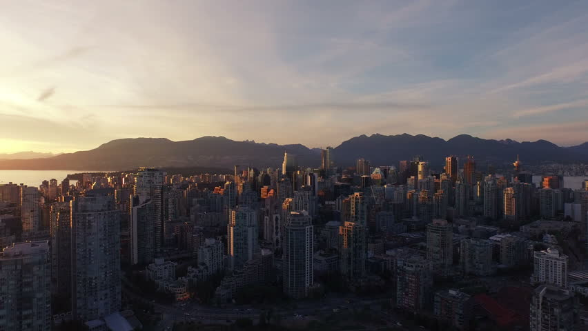 4K aerial vertical pan shot of Vancouver Skyline at sunset.