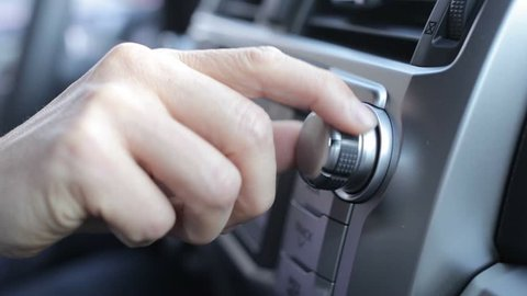 Tuning Radio Volume. Close up of hand adjusting car radio volume
