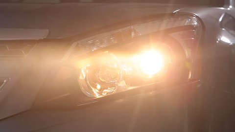 SANTIAGO, CHILE - A head-on, close up shot of a car's headlight. As the camera turns around the car, the bright light that blinded the scene slowly becomes less.