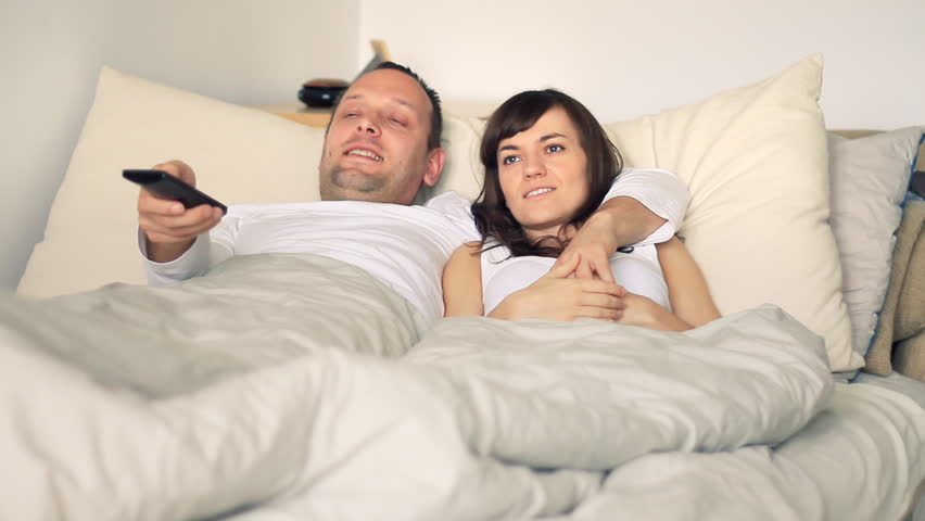 Young couple in bed watching tv