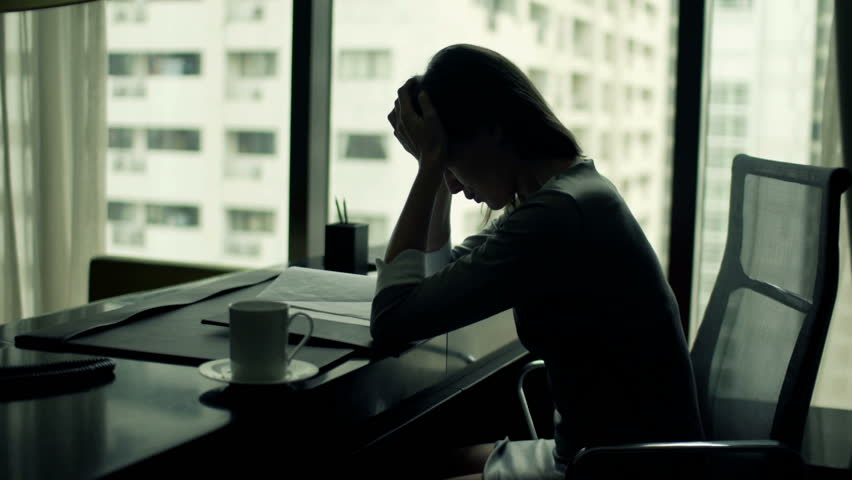 Silhouette of tired businesswoman having headache sitting at office desk
