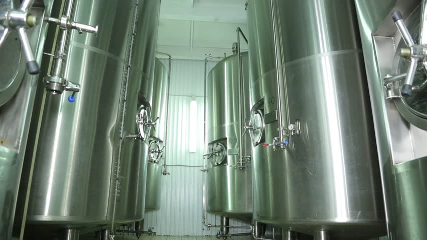 Beer production in the factory. Brewhouse . Malt . Beer is cooled in tanks. Chill . Fresh beer . Natural product. Fridge. Device for cooking .
