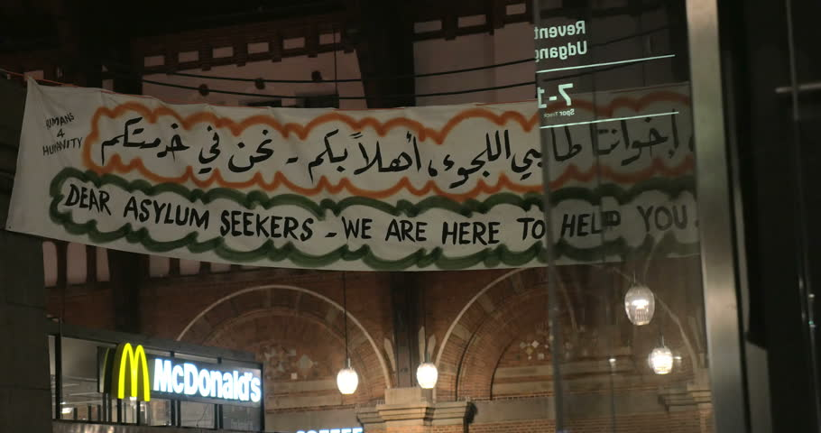 COPENHAGEN, DENMARK - SEPTEMBER 15, 2015: Banner Dear Asylum Seekers We Are Here to Help You in English and Arabic Script is hanged by charity collecting point in Copenhagen Railroad Station.