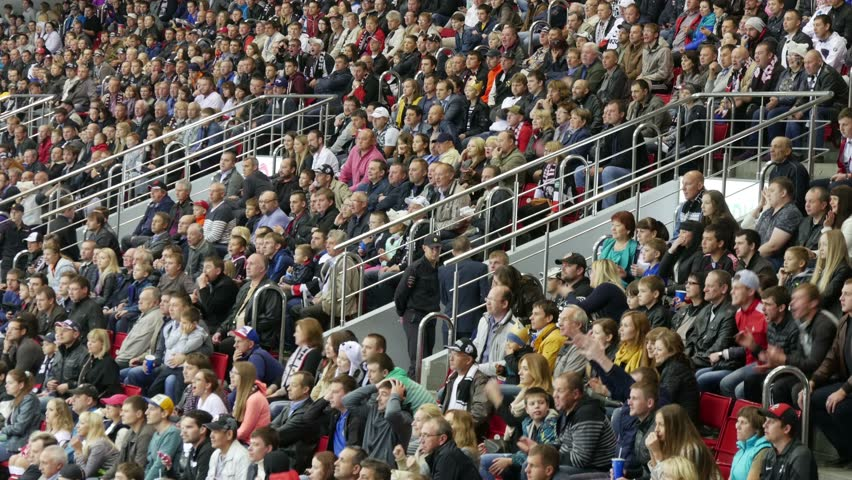 Chelyabinsk, Russia - September 19, 2015: Fans happily stand up from their seats when the team scores.