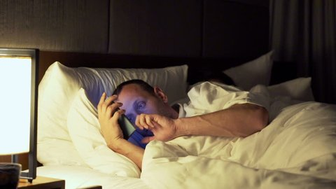 Couple in bed at night, man texting his lover on smartphone, his wife sleeping