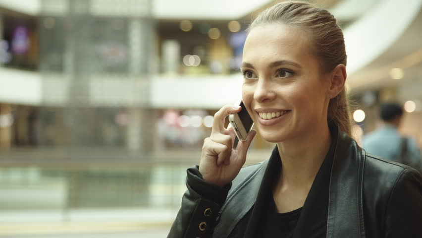 Beautiful girl with long hair, talking on the phone in the mall | Shutterstock HD Video #11817398