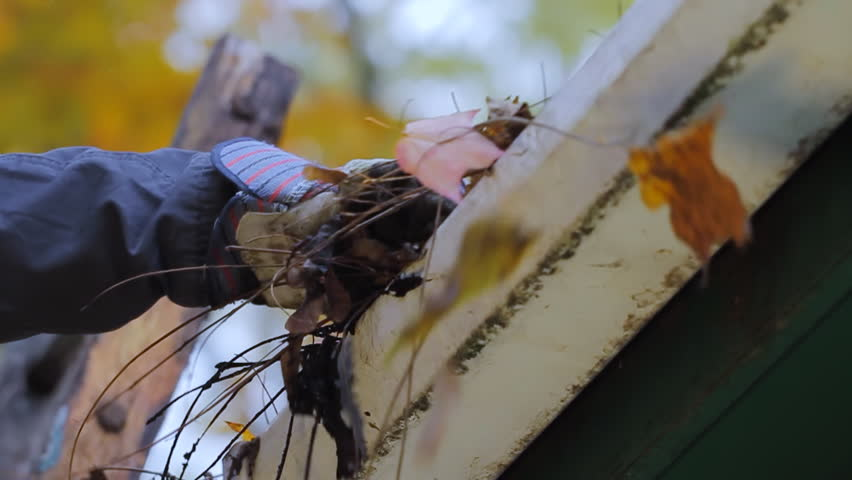 Gutter Cleaning Low Angle. camera dollies as person removes leaves and mud from gutters. slow motion