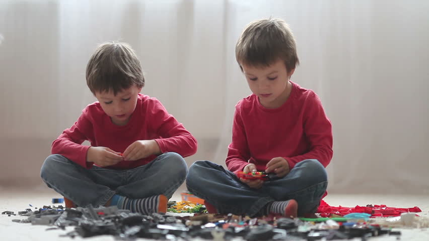 Little children playing with lots of colorful plastic blocks indoor, building a fire truck and a fire house, reading from a manual and imagining