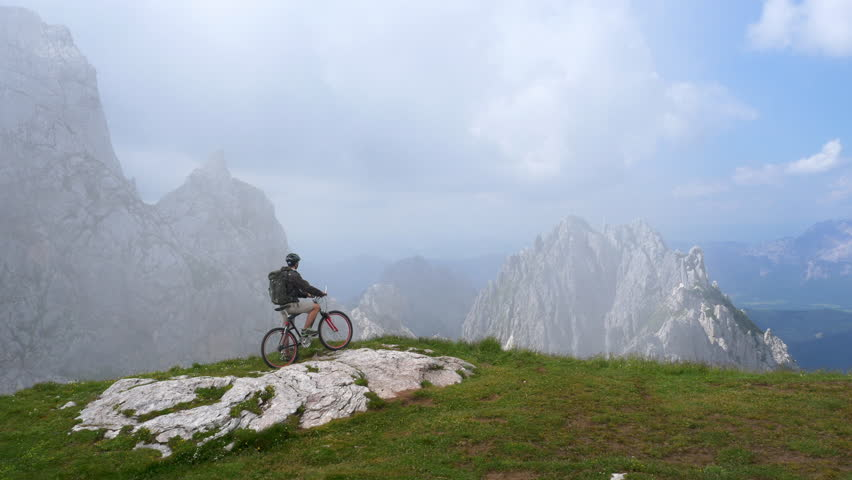 Aerial - Mountain biker looking at the view after reaching the summit