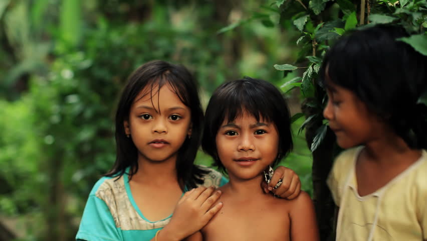 Three native Balinese girls posing playful for camera, changing places, laughing and having fun
