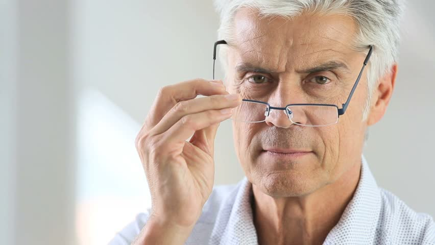 Senior man trying eyeglasses on in front of mirror