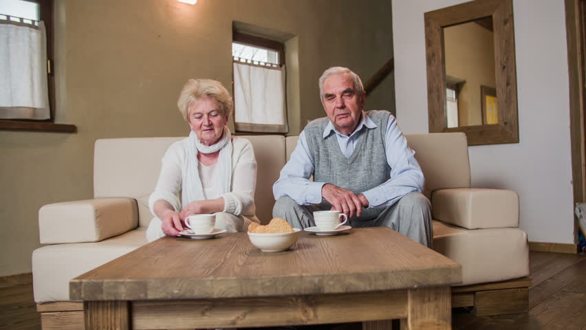 Grandparents in living room looking in camera 4K. Front view of old grandma and grandpa in big retro room sit on sofa and looking towards the camera. Tea cups on table.