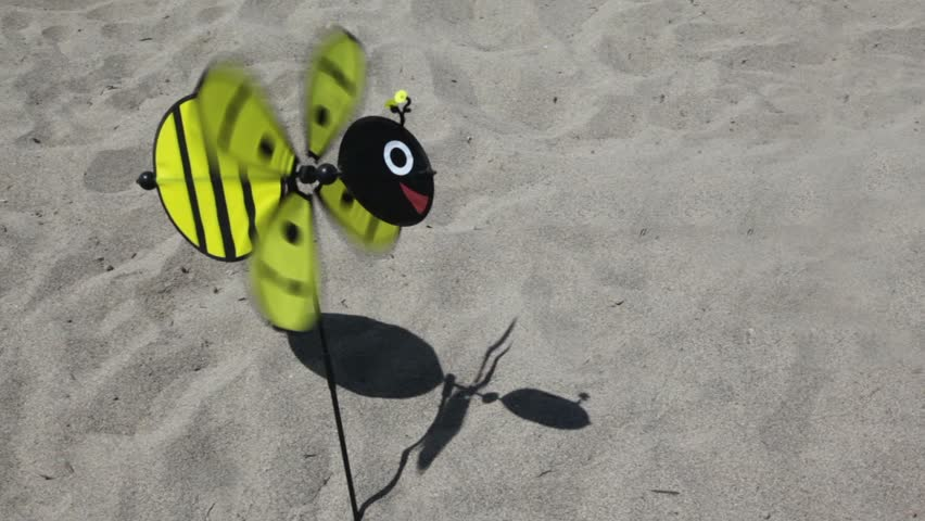Toy in the shape of a bee with a rotating propeller stuck in the ground, the propeller rotates, a toy sways